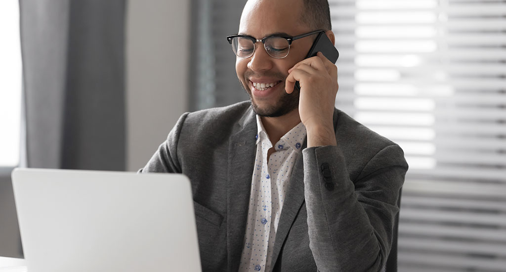 man on phone at computer receiving free small business account review